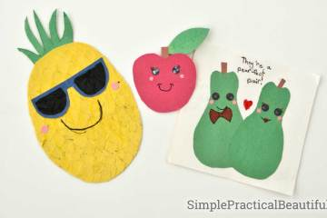 A pineapple, a watermelon, a banana, a pair of pears, a bunch of grapes, and an apple made of construction paper