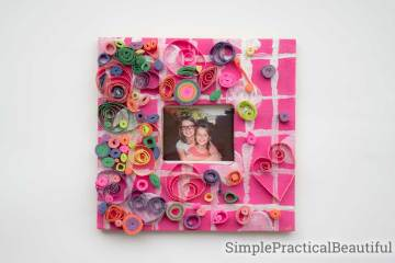 A wooden craft frame decorated with coiled paper quilling art