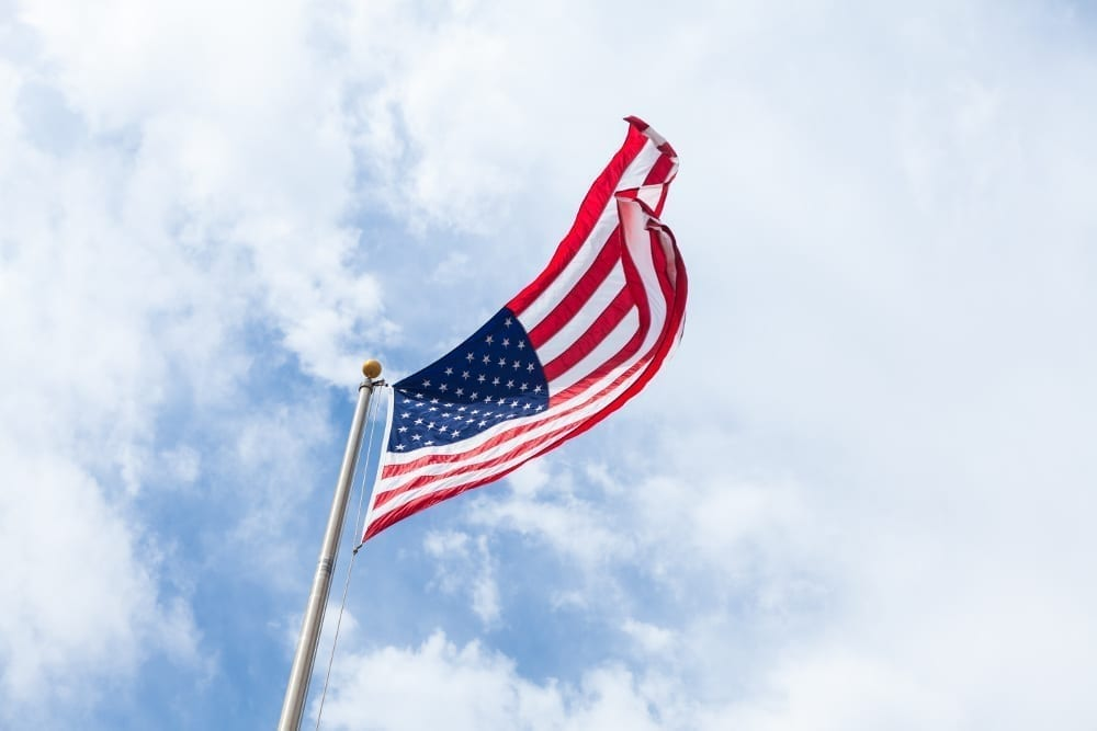 Looking up at an American flag flying at the top of a flapole