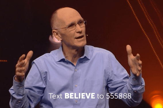 "Preacher with arms outspread, overset text reading ""Text BELIEVE to 555888"""