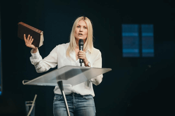 Holding a Bible and mic, Pastor Leanne preaches from behind a glass pulpit