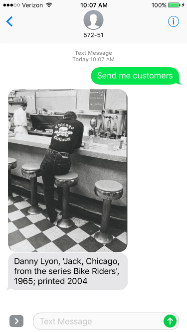 iPhone screenshot showing a 2004 Danny Lyon artwork of a Chicago Outlaw biker seated at a greasy spoon diner bar