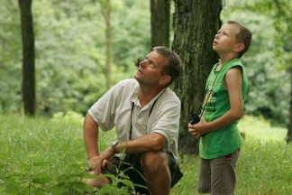 A father and son with hanging binoculars looking up in the woods
