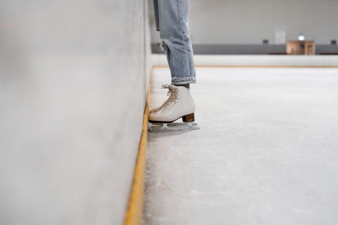 A person wearing white and gray skate shoes inside an ice skating rink