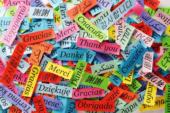 Colourful pieces of paper with Thank You in many languages printed on them