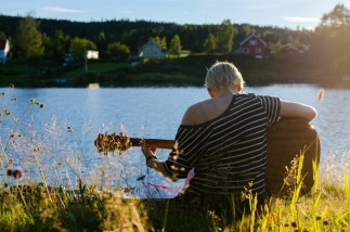 A girl plays the guitar by a river