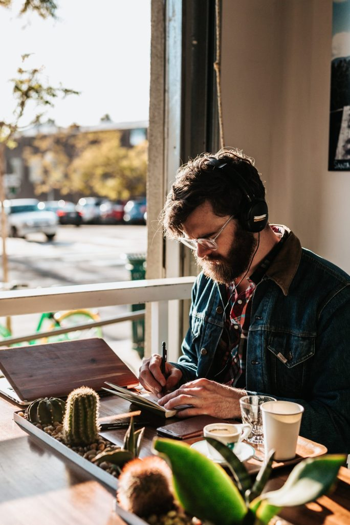 A man sitting at a table and writing while listening to headphones