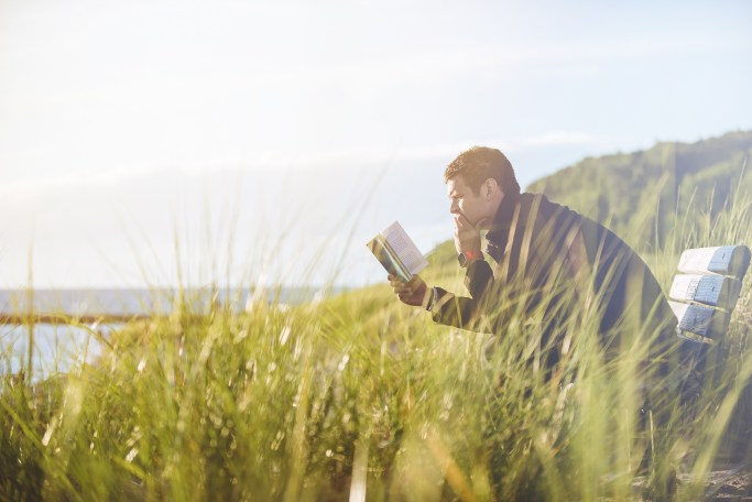 A man reading a book on a bench in a field by the sea