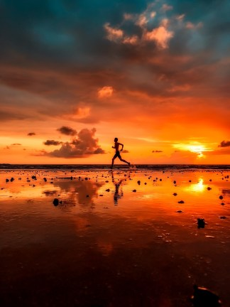 A man running on the beach at sunset