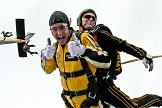 A man skydiving with a guide and smiling at the camera with thumbs up
