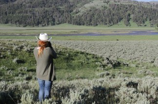 A woman photographs wildlife from afar in a green valley with a river