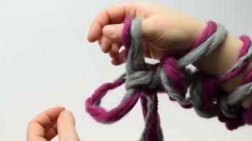 Die Masche, die über die Hand gezogen wird, loslassen und die aus dem Arbeitsfaden entstandene Schlinge greifen und hochziehen.