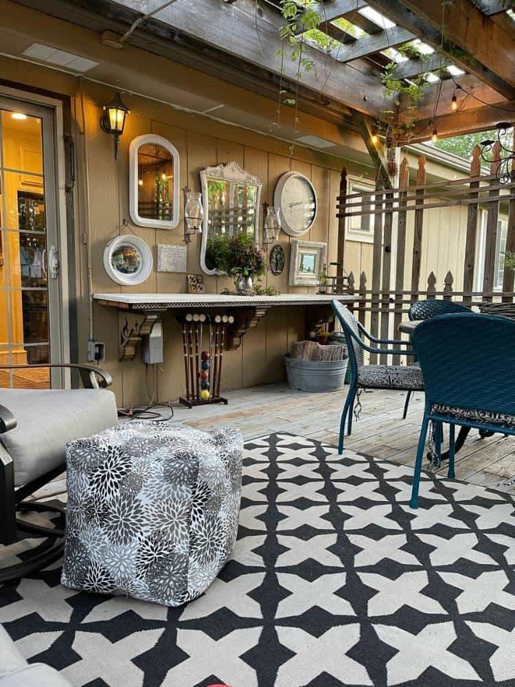 Outdoor patio with pergola roof with a wall of mirrors and a DIY pouf ottoman