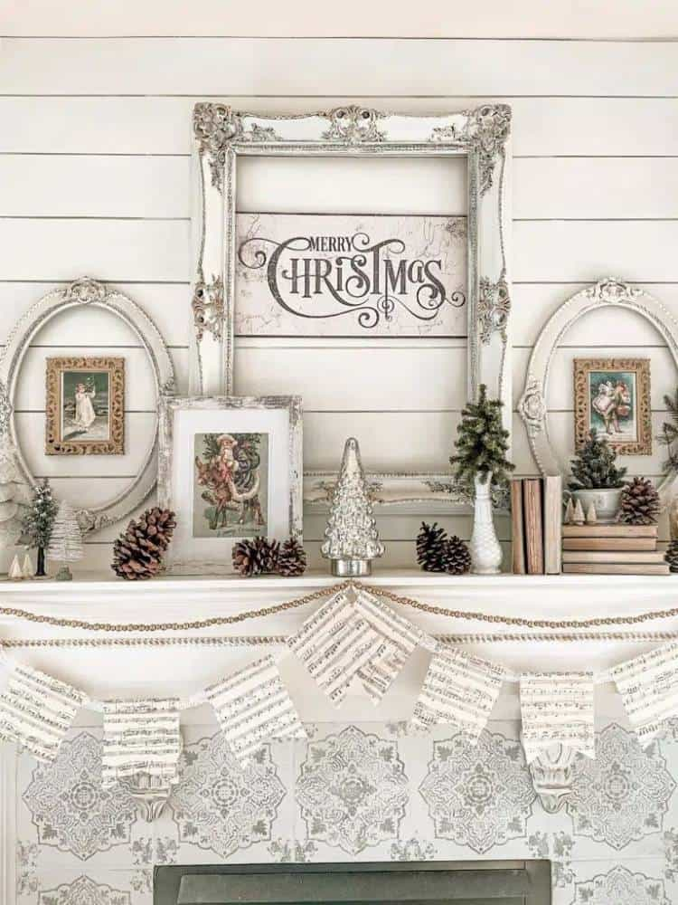 Fireplace mantel with white shiplap wall decorated for Christmas with open picture frames, pinecones, and miniature trees on stacked vintage books