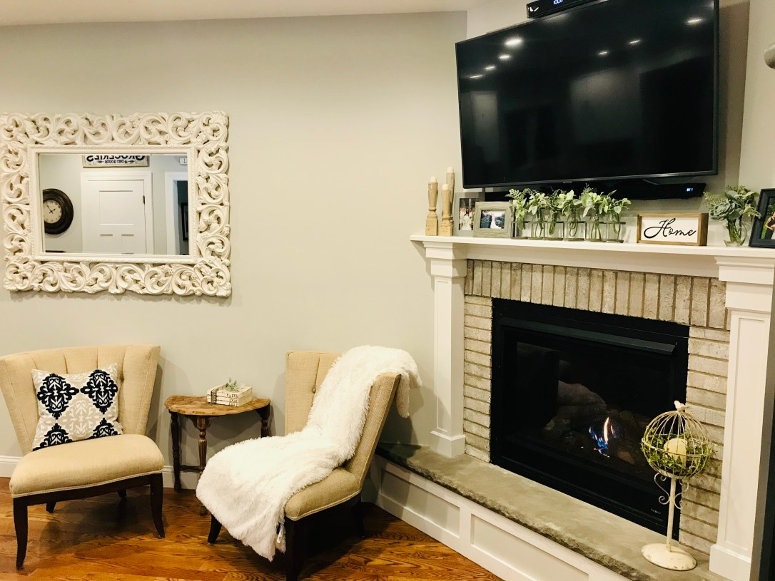 Living room with white washed brick fireplace, two sitting chairs, navy and white pillow and white faux fur blanket.
