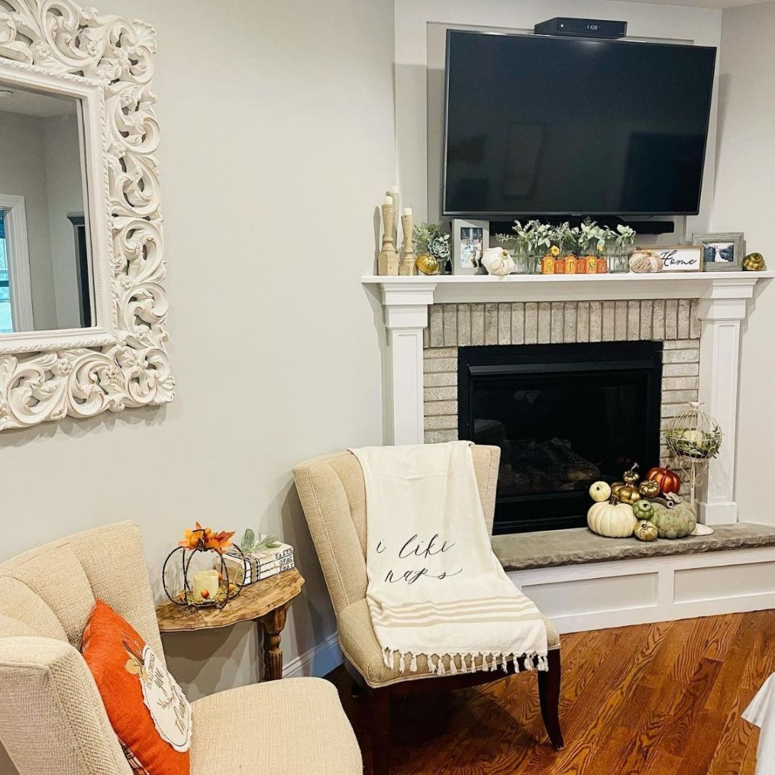cozy white washed brick fireplace with ivory, gold and green faux pumpkins. Two ivory sitting chairs with a cream colored throw blanket and an orange seasonal pillow.