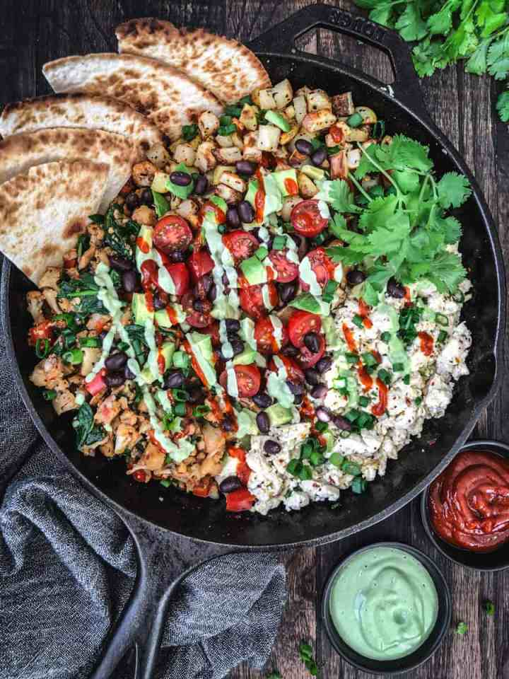vegan breakfast has with tofu scramble in a skillet with tortillas