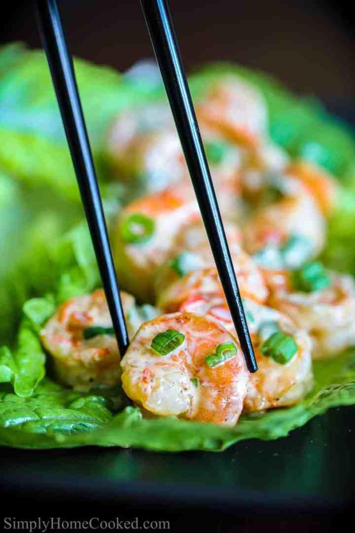 close up image of grilled bang bang shrimp on a bed of lettuce leaves with black chop sticks