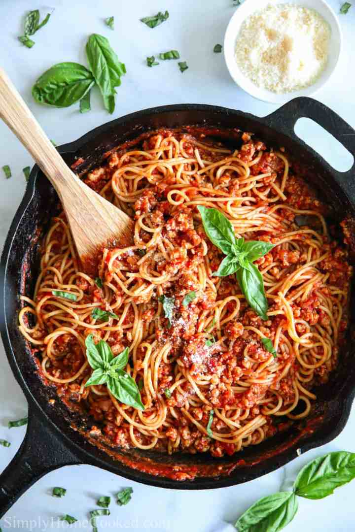 overhead image of spaghetti and meat sauce in a cast iron pan with fresh basil on top