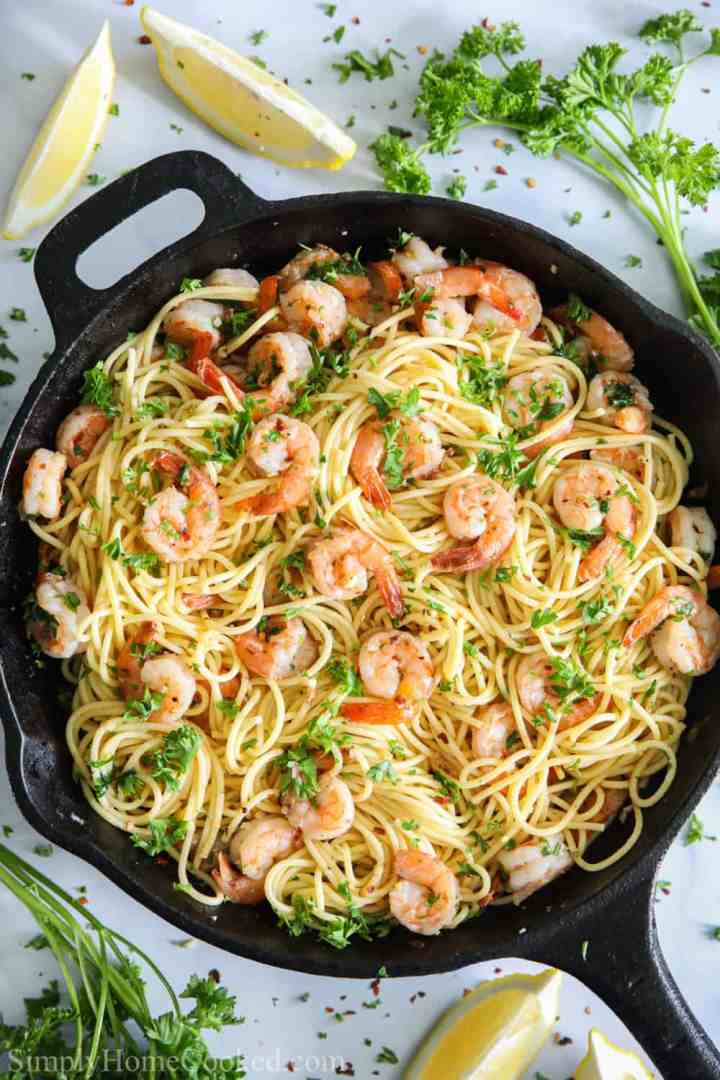 an overhead image of shrimp scampi pasta in a cast iron pan with red pepper flakes and chopped parsley on top and 2 lemon wedges beside it