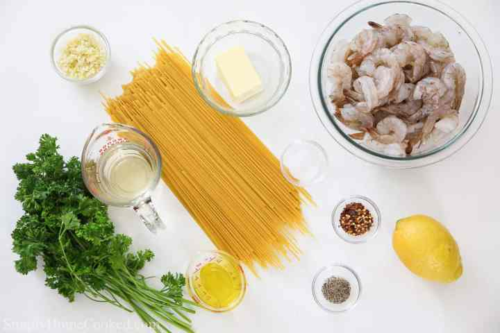 an overhead image of ingredients for shrimp scampi pasta on a white background