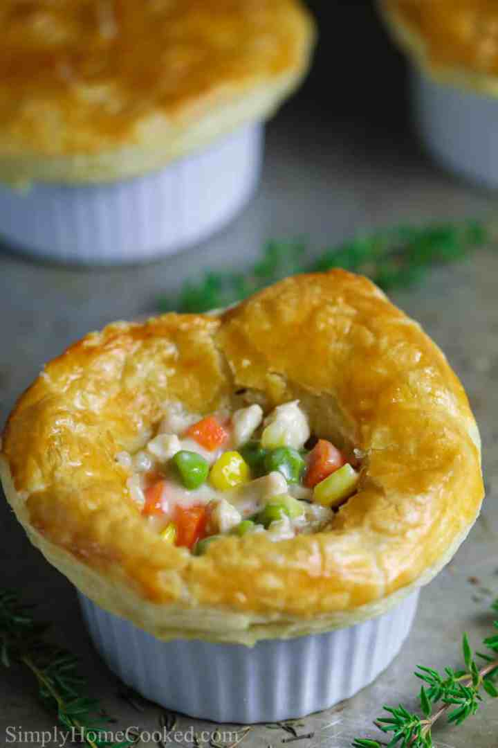 a close up photo of a mini homemade chicken pot pie topped with puff pastry with the center opened up and chicken, corn, peas, and carrots inside