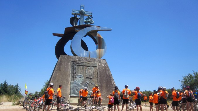Modern religious sculpture on Monte do Gozo with a group of bikers in front of it