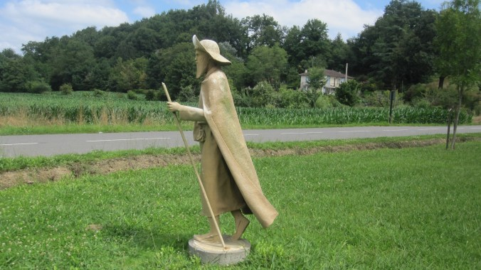 Statue of a pilgrim with staff, shell and the typical pilgrim's hat