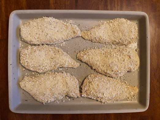 After going through the assembly line of breaded the chicken, I lay them all out on a tray when they are done. Then, I always sprinkle the left over breadcrumbs on top.
