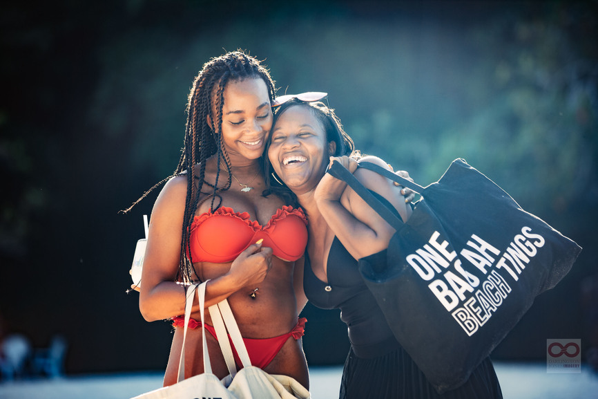 women smiling with beach tote bag
