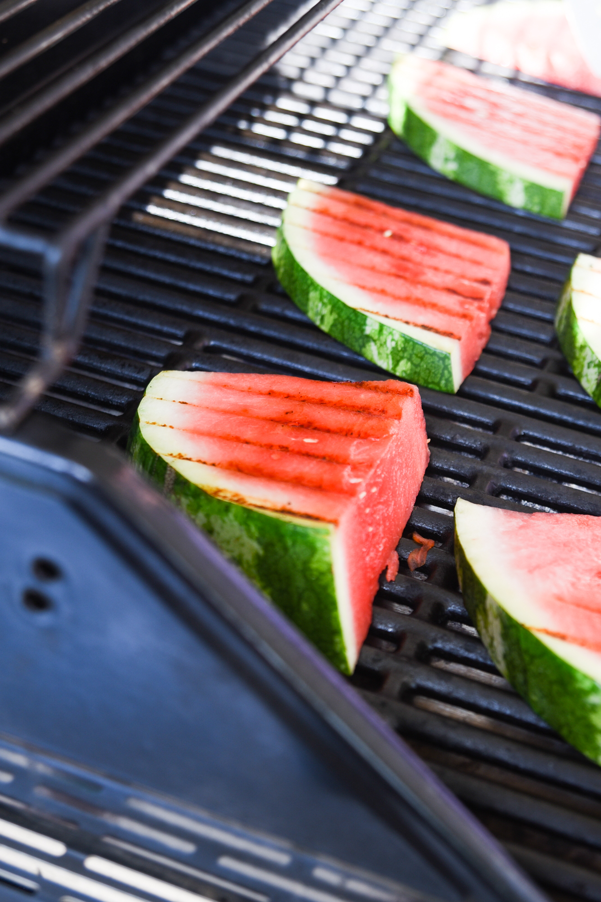 Slices of watermelon on a grill with grill marks