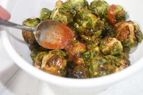 pouring sauce on top of brussel sprouts