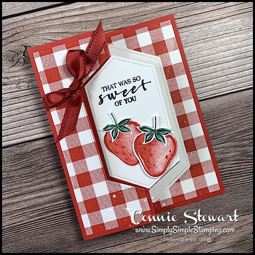 This creative swinging card features a red and white gingham background with strawberries stamped as the focal point.