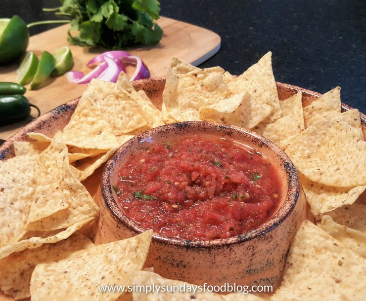 A bowl of salsa surrounded by tortilla chips with fresh ingredients in the background