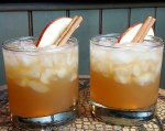 Two glasses of Apple Cider Bourbon garnished with a fresh apple wedge and cinnamon stick