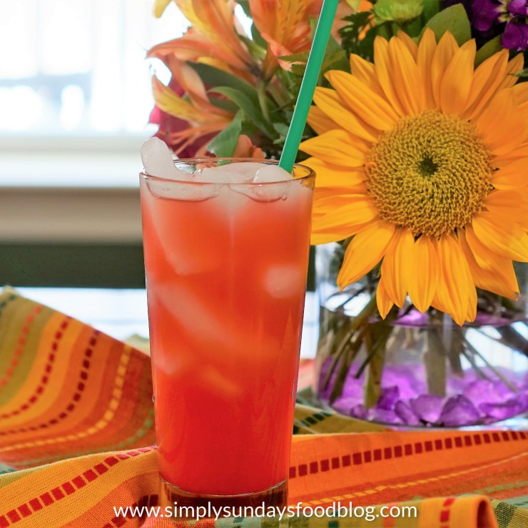 A tall glass of fruit juices on a colorful cloth with fresh flowers in the background