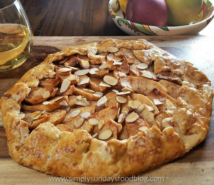 A rustic apple crostata on a cutting board with a glass of white wine and a bowl of apples in the background