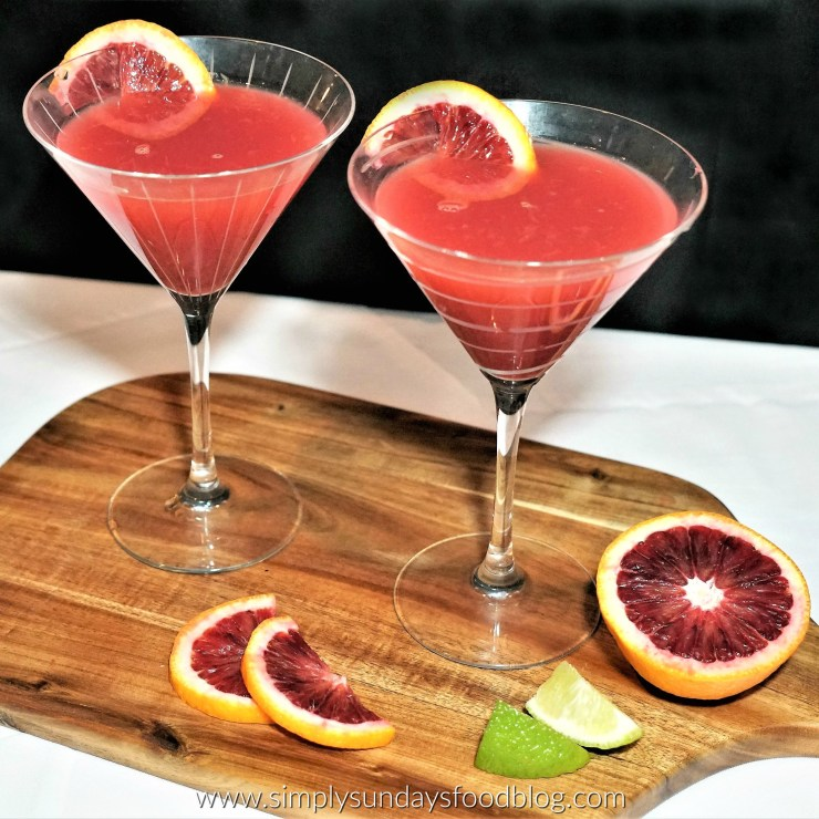 Two martini glasses filled with blood orange martinis, garnished with blood orange wheels. They sit on a wooden board with slices of fresh blood orange and limes