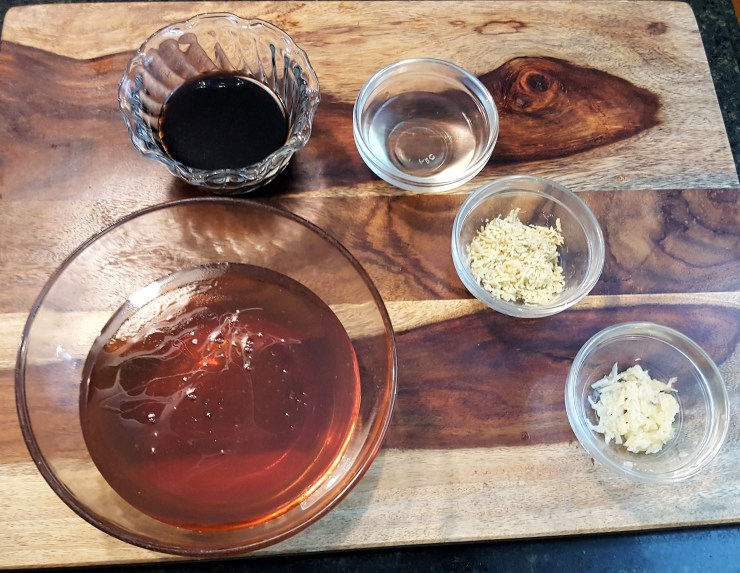 Bowls filled with soy sauce, honey, rice wine vinegar, grated fresh ginger and grated garlic