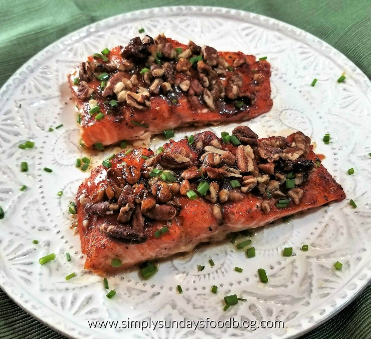 Honey and maple glaed salmon fillets topped with crunchy pecans sprinkled with fresh green chives served on a white plate