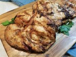 Tender marinated and juicy grilled chicken on a cutting board with parsley