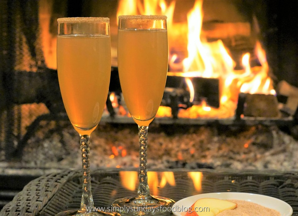 Two champagnes flutes of crisp, bubbly champagne topped with a flavorful splash of cider and rimmed in cinnamon sugar in front of a fire