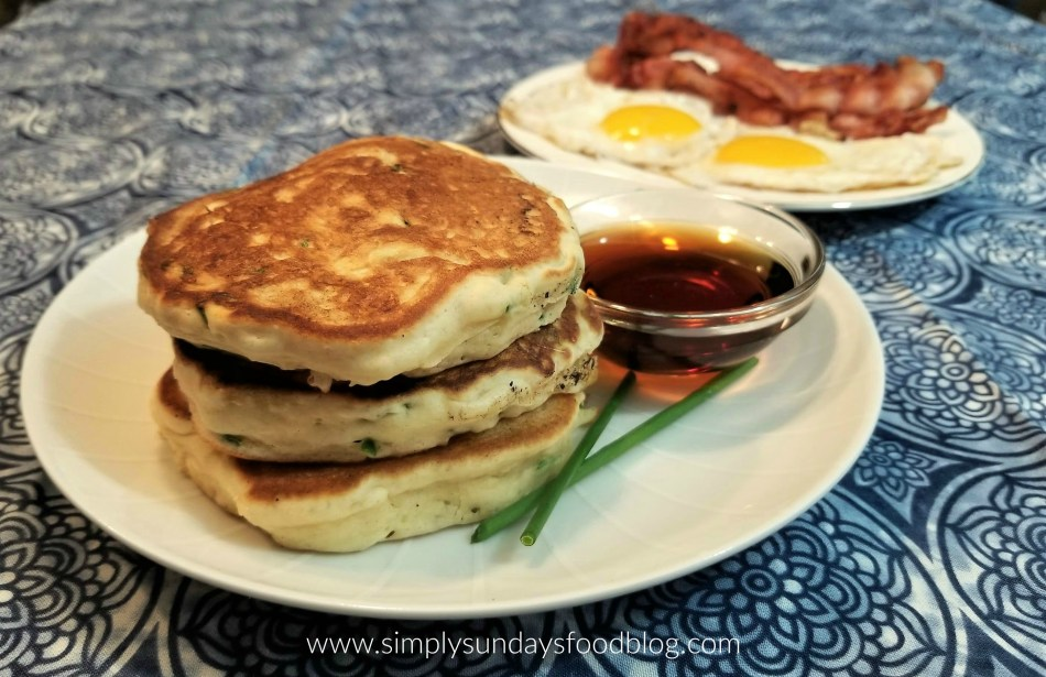 Cheddar Chive pancakes on a plate with maple syrup and fried eggs and bacon in the backround