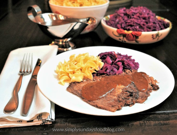 Tender German style pot roast topped with a ginger snap gravy served with a side of German braised red cabbage and egg noodles