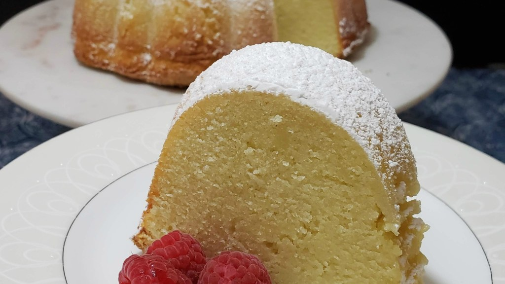 A slice of pound cake dusted with powdered sugar on a plate with fresh raspberries. Bundt cake on platter in background