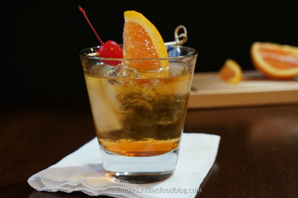 Old Fashioned whiskey drink on a cocktail napkin garnished with an orange wedge and a maraschino cherry