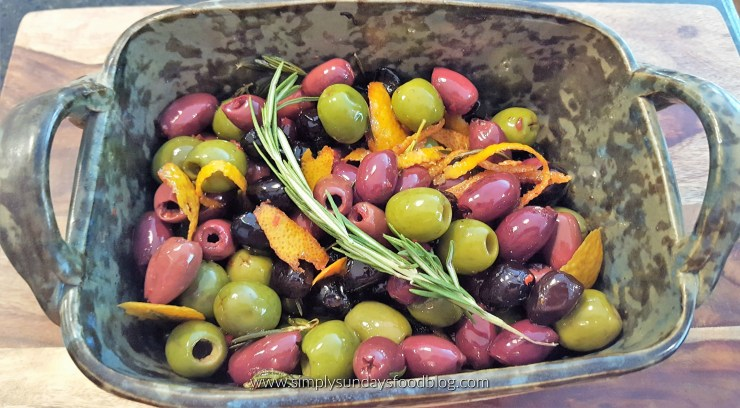 Bowl of citrus marinated olives with a sprig of fresh rosemary