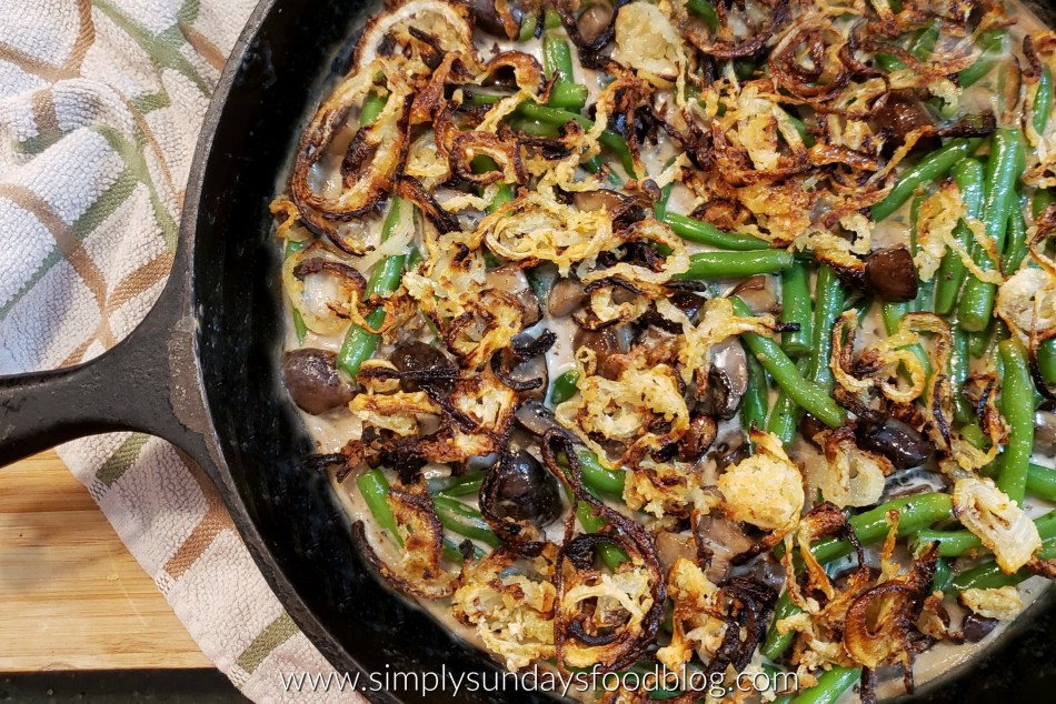 Fresh green beans and mushrooms in a creamy sauce topped with crispy oven baked onion rings in a cast iron pan on a board