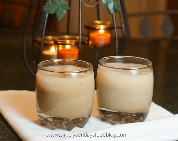 Two short cocktail glasses with Toasted Almond cocktails on a white cloth with muted candles in the background