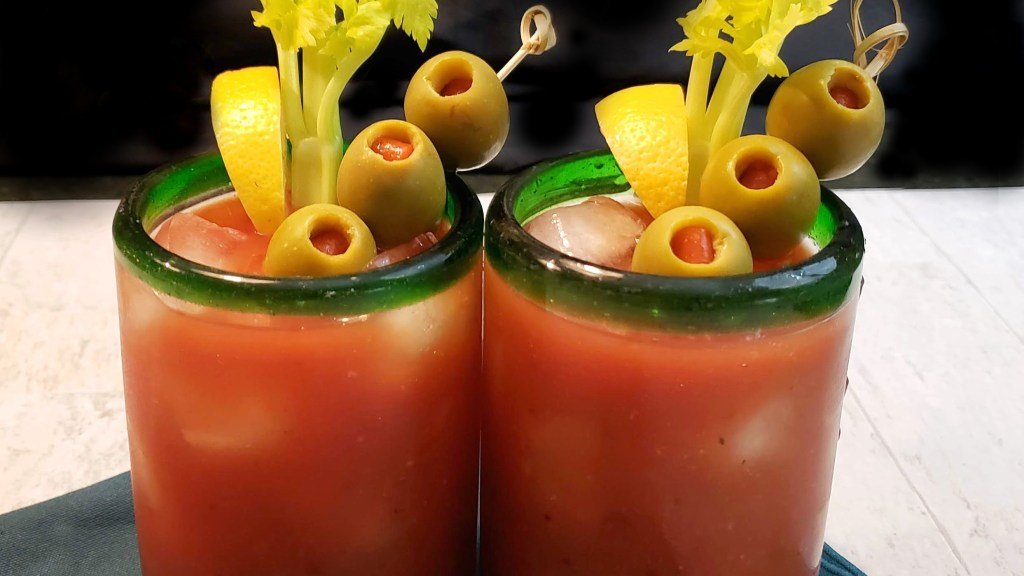 Two glasses of Bloody Mary cocktail garnished with green olives, fresh lemon wedges and a stalk of celery